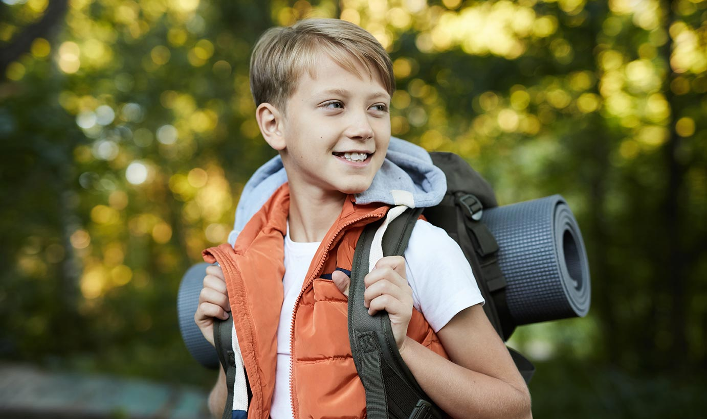 A young boy with healthy teeth wears an orange vest and smiles happily during a camping trip.